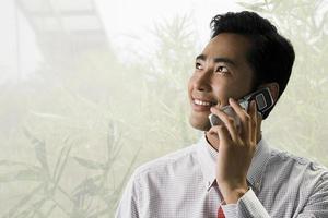 ung affärsman som använder en mobiltelefon foto