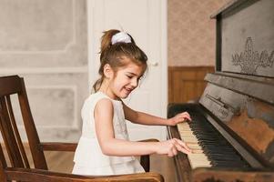 profil för liten flicka i vit klänning som spelar piano. foto
