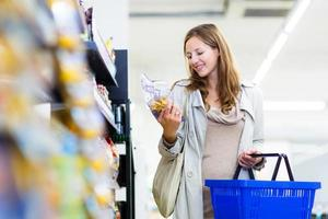 vacker ung kvinna som shoppar i en livsmedelsbutik foto