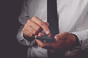 affärsman som arbetar på den smarta mobiltelefonen foto