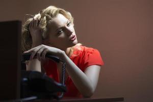 uttråkad kvinnlig sekreterare med telefon foto