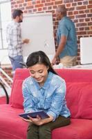 avslappnad kvinna som använder digital tablet på soffan foto
