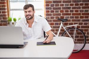avslappnad designer som använder grafikplatta och bärbar dator foto
