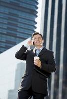 attraktiv affärsman i kostym och slips som pratar i mobiltelefon foto