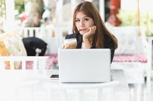 asien ung affärskvinna som sitter på café med laptop foto