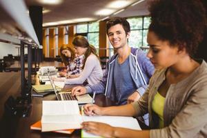 student tittar på kameran medan han studerar med klasskamrater foto