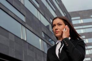 vacker affärskvinna i telefon på modern byggnad foto