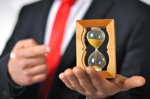 man i kostym med slips som håller ett timglas