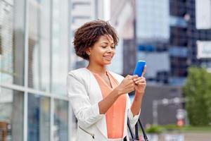 glad afrikansk affärskvinna med smartphone foto