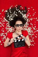 tjej med 3d-glasögon, popcorn och clapboard som ber om tystnad foto