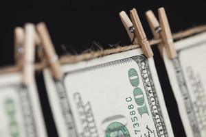 hundra dollarsedlar som hänger från klädstreck på mörk bakgrund