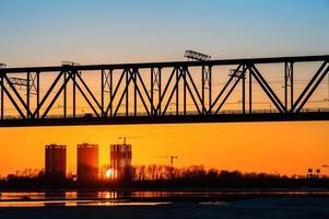 järnvägsbro och byggarbetsplats på flodstranden foto