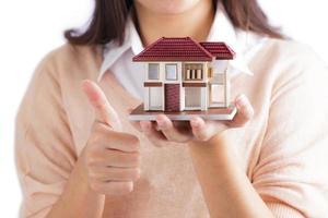 kvinna som håller litet hus foto