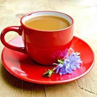 cikoria dryck i röd kopp med blomma ombord foto