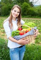blond kvinna med grönsaker färska från fältet foto