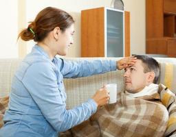 kvinna som tar hand om sjuk man foto
