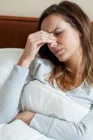 sjuk kvinna med huvudvärk foto