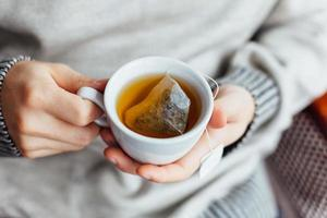 närbild av mannen som håller en kopp varmt te