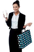 dam som håller kaffekopp och shoppingväska foto