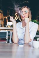 kvinna röker en cigarett på ett café foto