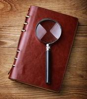anteckningsbok med en förstoringsglas på träbord foto