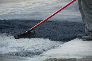 arbetare som krattar asfalt foto