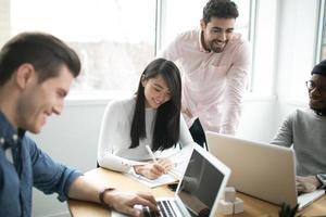 unga yrkesverksamma som arbetar på bärbara datorer på ett kontor foto