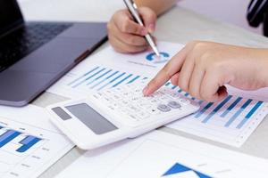 affärsperson använder kalkylator för att analysera ekonomiska data på jobbet foto