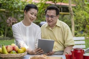 äldre par sitter utomhus och tittar på surfplatta foto