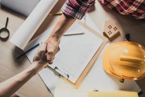 en ingenjör och byggentreprenör skakar handen över ett byggbud foto