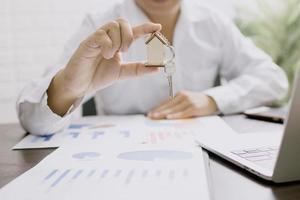 fastighetsaffärsman som håller nyckelring av modellhemmet foto