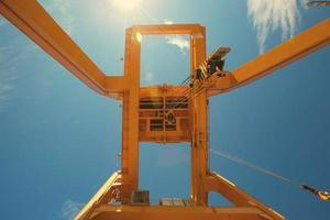 konstruktionskran för brobyggnad på bakgrund med blå himmel foto