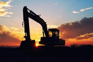 grävmaskin silhuett i solnedgång ljus. foto