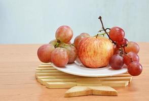 röd druva och äpple på maträtt foto