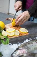 frische forelle mit citron på einem holztablett foto