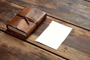 notbook och ett pappersark på träbord åt sidan foto