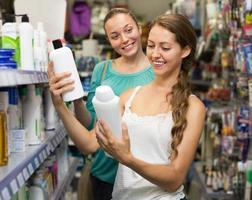 kvinna att välja schampo i butik foto