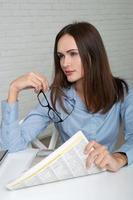 kvinna som håller i en hand en tidning foto