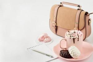 varm choklad med marshmallows, anteckningar och kvinnors handväska på foto
