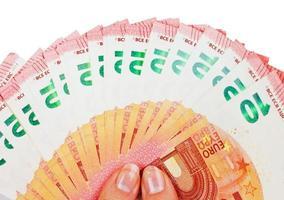 två händer som håller tio eurosedlar isolerad på vitt foto