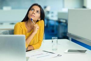 fundersam affärskvinna som sitter på sin arbetsplats foto