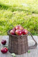 korg med äpplen på ett träbord foto