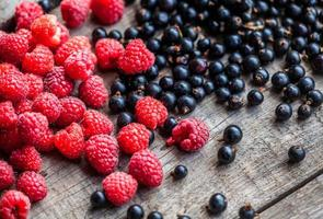 närbild svarta vinbär och hallon på träbord foto