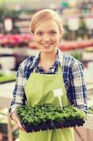 glad kvinna som håller plantan i växthus foto