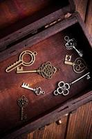 vintage nycklar inuti gamla skattkista på trä bakgrund foto