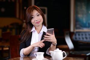 vacker ung asiatisk tjej med smart telefon på ett kafé foto