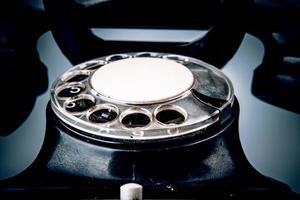 gammal svart telefon med damm och repor på vit bakgrund