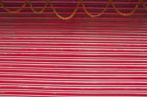 rödmålad korrugerad metalldörr och blommig girland foto