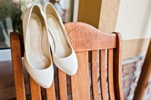 grädde bröllop skor av bruden på trästol foto