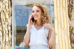 vacker ung kvinna med shopping nära butiken foto